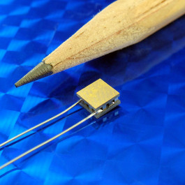 image of micro thermoelectric TEC module 00701-9B30-22RU4 shown next to pencil tip for scale