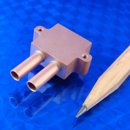 Iso view of small mini Liquid cold plate machined from copper for cooling semiconductors, TECs, lasers, etc. Shown with pencil tip for scale
