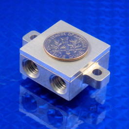 Iso view of small mini Liquid cold plate machined from aluminum for cooling semiconductors, TECs, lasers, etc. Shown with coin for scale