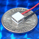 image of mini micro peltier TEC cooler module 00711-5A30-12CU4 shown sitting on USA Dime 10 cent coin for scale