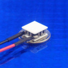 image of mini micro peltier TEC cooler module 00711-5L31-04CB shown sitting on USA Dime 10 cent coin for scale