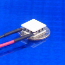 image of mini micro peltier TEC cooler module 00711-5L31-06CB shown sitting on USA Dime 10 cent coin for scale